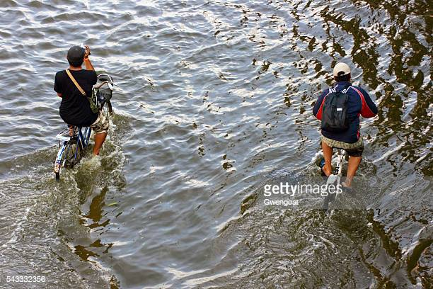 two guys riding their bicycle during the flood - gwengoat stockfoto's en -beelden