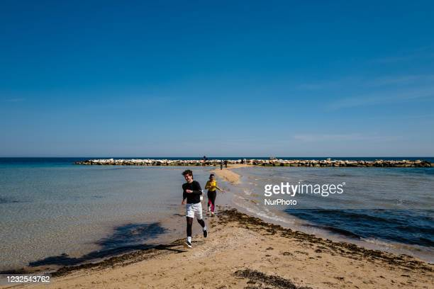 Two guys run on the beach of Pane e Pomodoro on the first day in the orange zone after more than a month in Bari on April 26, 2021. Italy tries to...