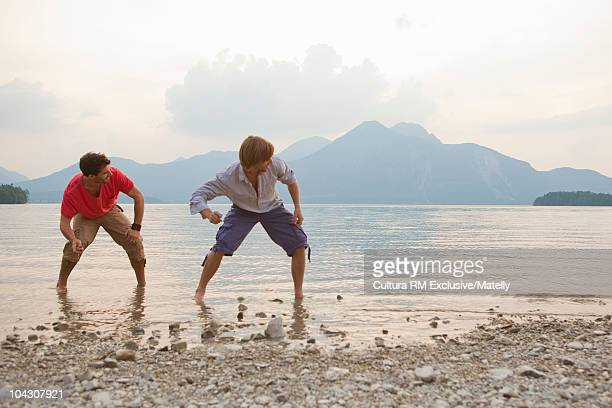 Two guys throwing stones in a lake