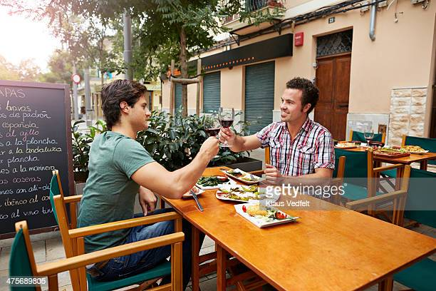 two guys toasting in redwine at restaurant - tapas stock photos and pictures