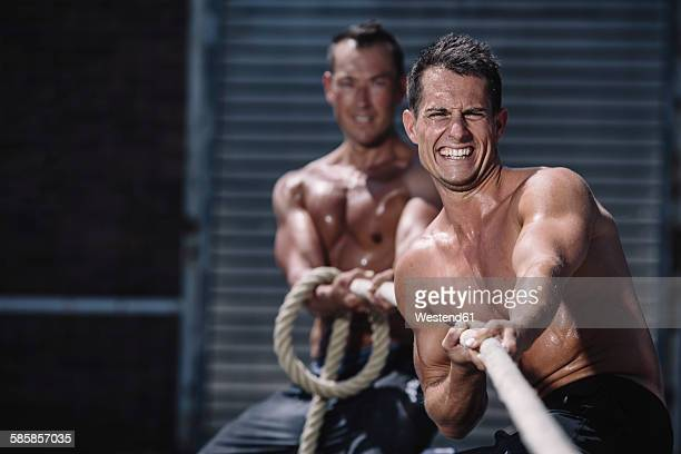 Two gym athletes pulling rope