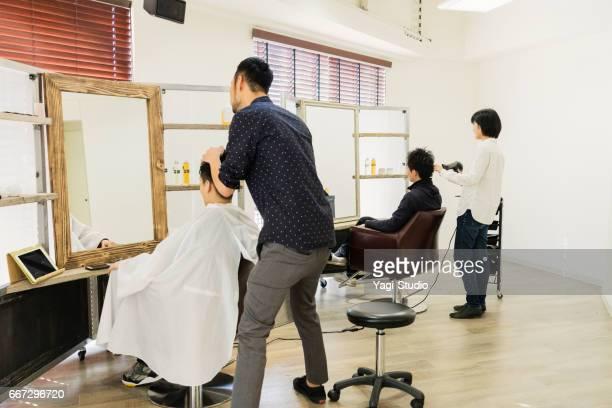 自分のヘアサロンで働く 2 つの髪スタイリスト オーナー