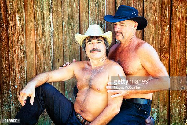 Two hairy bear affectionate cowboys against wooden fence