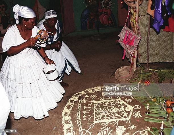 Two Haitian mambo or women priests perform ritual prayers to the voodoo god of work Kousin during a voodoo ceremony 08 May 2000 in Sarthe north of...