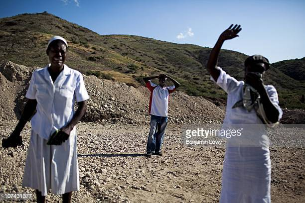 Two Haitian women weep while standing on top of a mass grave housing over 100,000 victims of the Haitian earthquake located on the outskirts of Port...