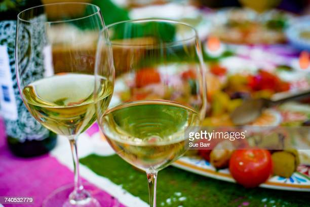 Two half filled wine glasses on table, food on plate behind, close-up
