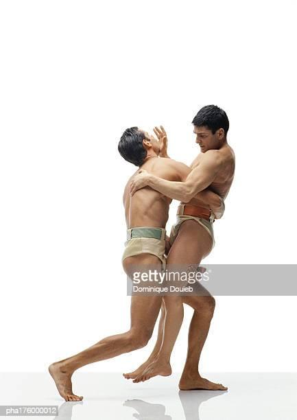 Two half-nude men wrestling