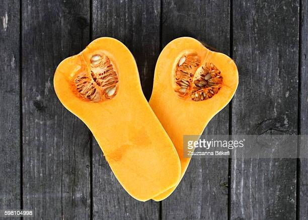 Two halfs of a butternut squash on a old wooden garden table