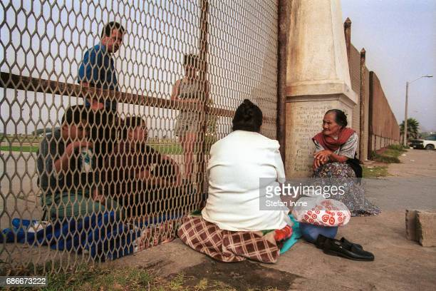 Two halves of a family gather to share news and a meal on opposite sites of the USMexico border fence where the boundary meets the Pacific Ocean