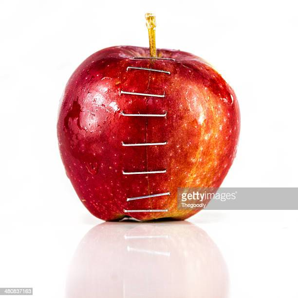 Two halves of an apple stapled together