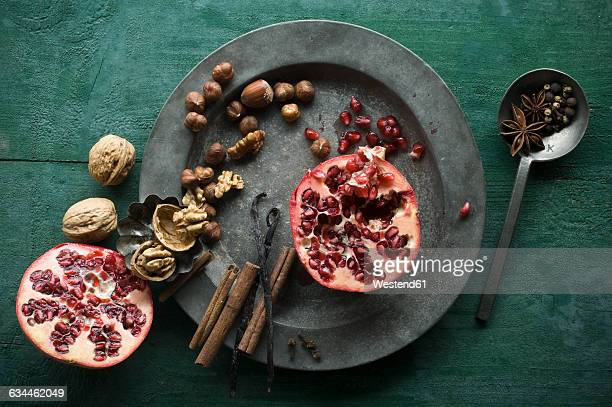 two halves of pomegranate, different spices and nuts on tin plate - gewürznelke stock-fotos und bilder