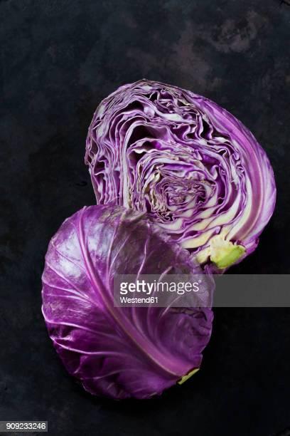 Two halves of purple Sweetheart Cabbage on dark ground