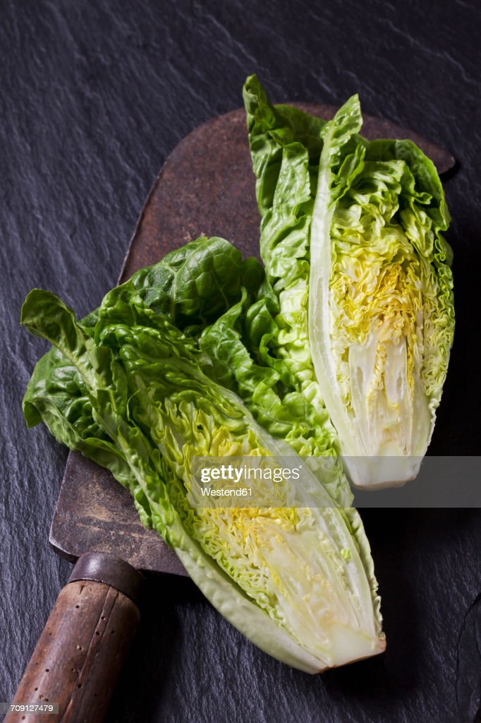 Two halves of romaine lettuce and an old knife on slate : Stock Photo