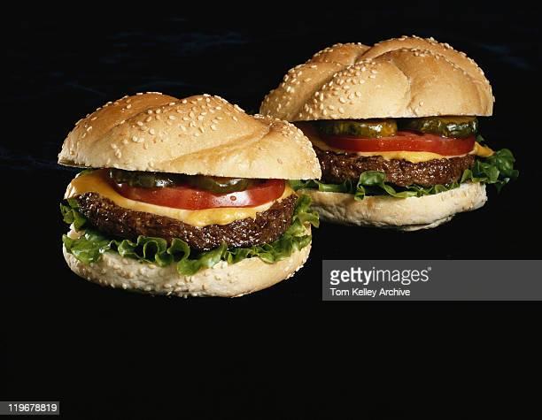 Two hamburgers on black background, close-up