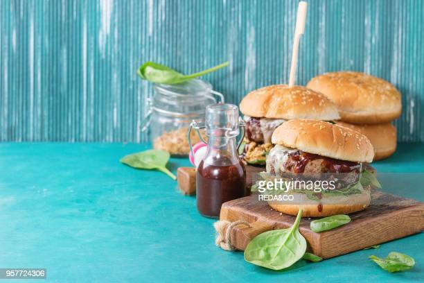 Two hamburgers with beef burger cutlet fried onion spinach ketchup sauce and blue cheese in traditional buns served on wood chopping board over...