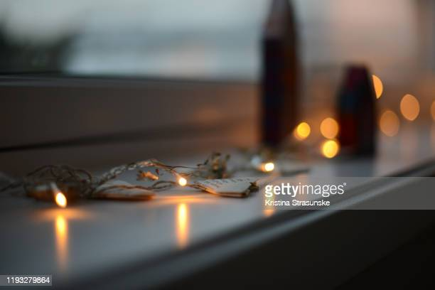 two handmade wooden and painted decorative christmas houses in a windowsill by a chain of christmas lights - kristina strasunske stock pictures, royalty-free photos & images