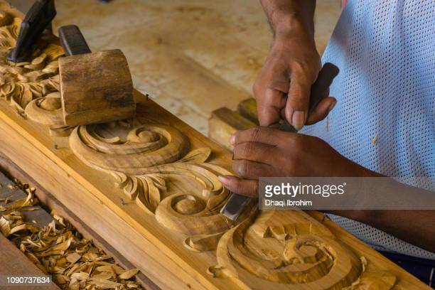 Two hands are carving wood