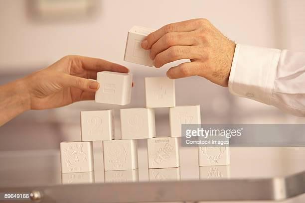 two hands building blocks