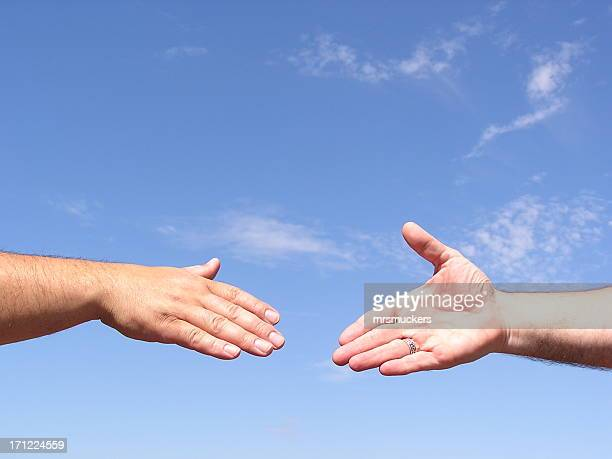 Two hands coming together for a handshake in front of sky