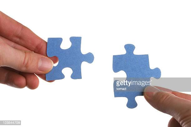 Two hands coming together to solve a puzzle