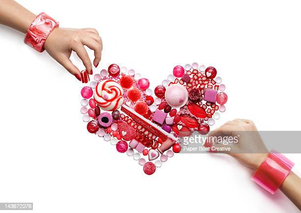 two hands forming a pink and red candy heart