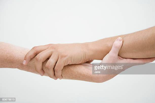 Two hands griping each other's arms, unrecognizable people