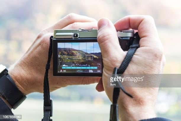 two hands hold a camera with landscape motif on display - digital viewfinder stockfoto's en -beelden