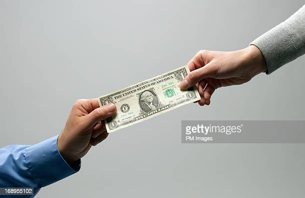 Two hands holding a dollar