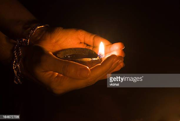 Two hands holding a small lit oil lamp in the dark