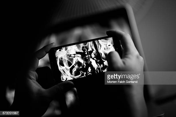 Two hands holding a smart phone taking a picture of a manga figurine with a fiery background