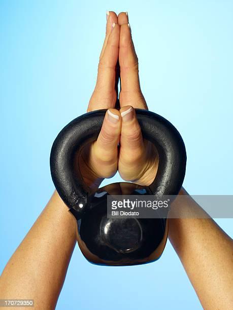 two hands holding black kettlebell