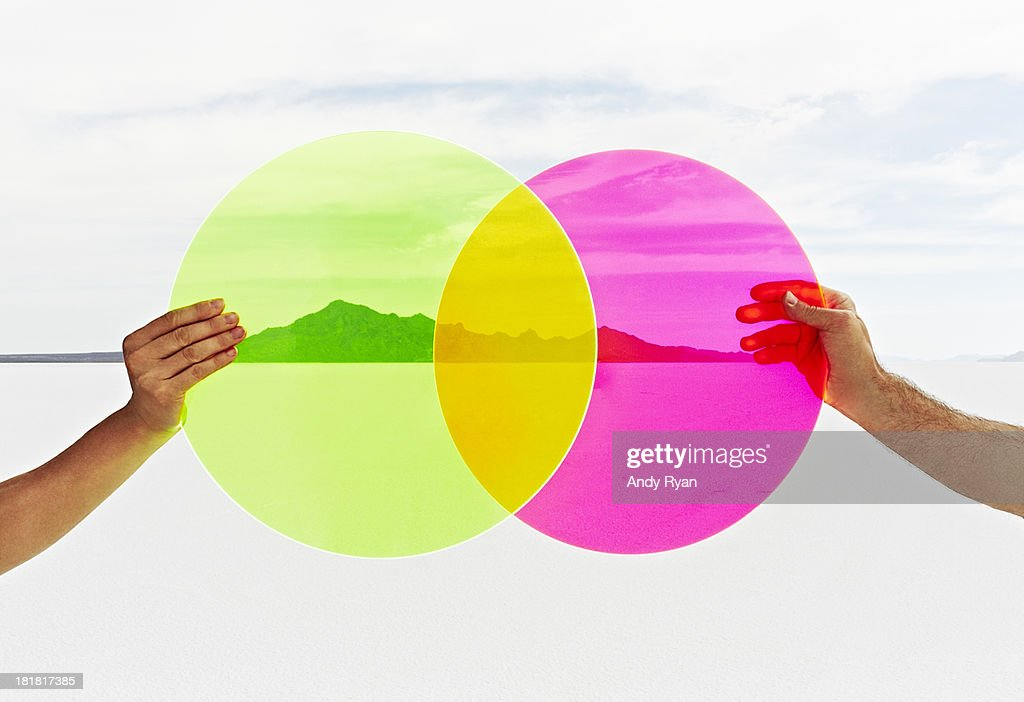 Two hands holding colored circles in landscape. : Stock Photo