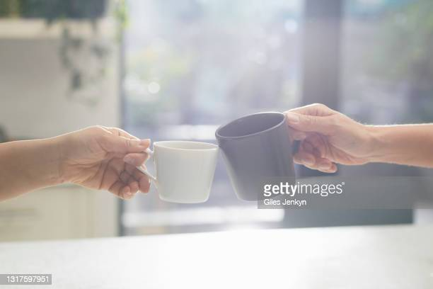 two hands holding cups to toast - honour stock pictures, royalty-free photos & images