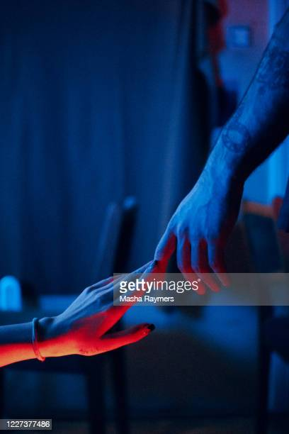 two hands holding in blue and red light  close up view - editorial stock pictures, royalty-free photos & images