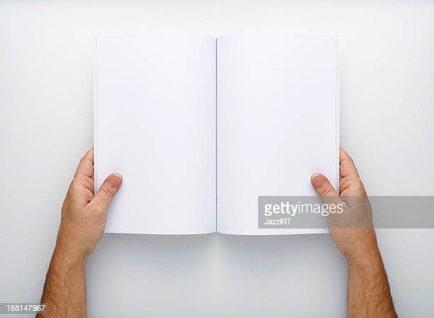 two hands holding open a blank magazine - magazine page stock photos and pictures