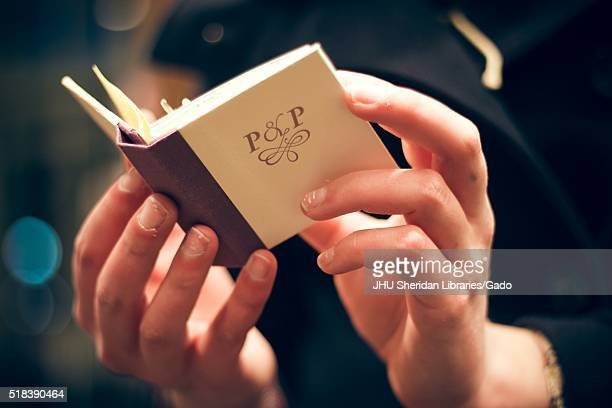Two hands holding open a small book with a creamcolored cover and a maroon spine with the letters P and P 2016