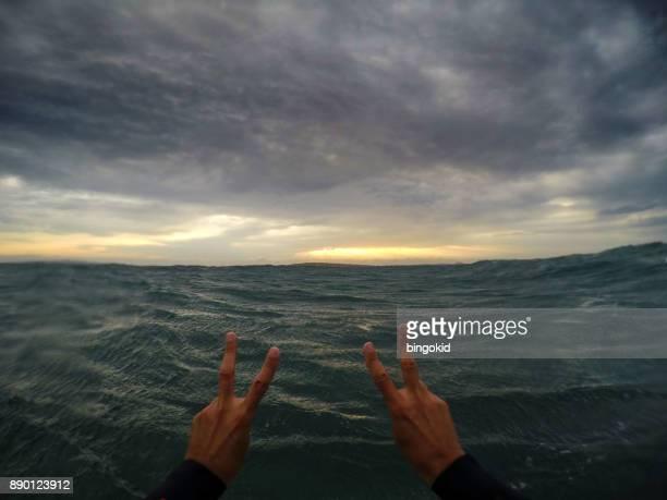 Deux mains tenant le signe de la victoire en mer