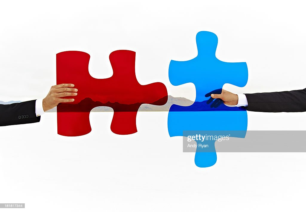 Two hands join colored puzzle pieces. : Stock Photo