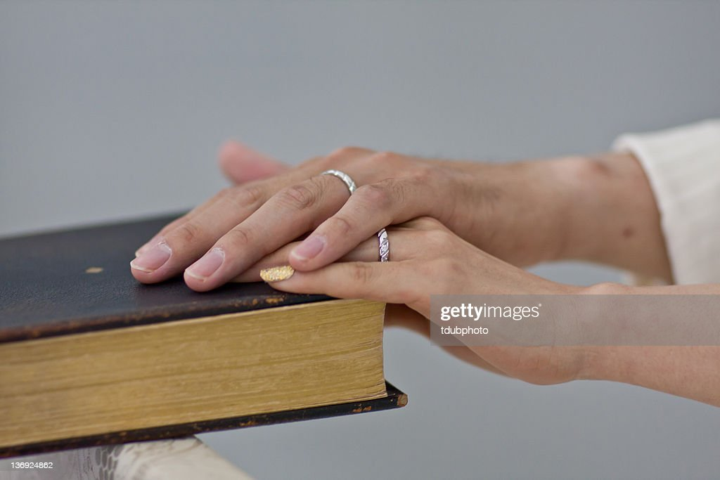 two hands on bible as they make their wedding vows stock photo