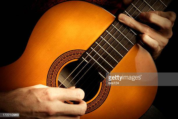 two hands playing acoustic guitar - classical guitar stock photos and pictures