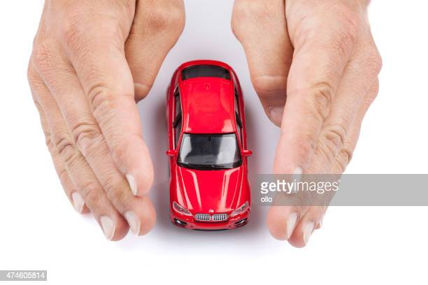 Two hands protecting a red BMW toy car