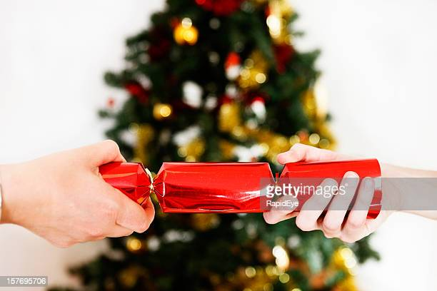 Two hands pull a bright red Christmas cracker