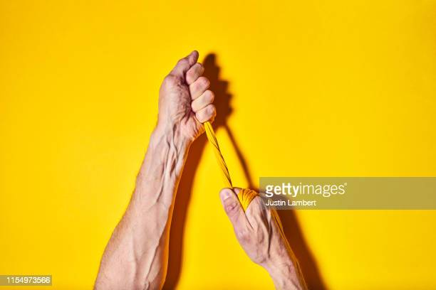 two hands pulling apart yellow yarn on a bright yellow backdrop - resilience stock photos and pictures