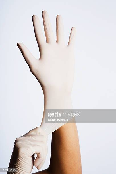 Two hands putting latex gloves on