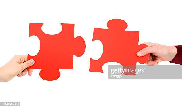 Two hands putting two puzzle pieces together