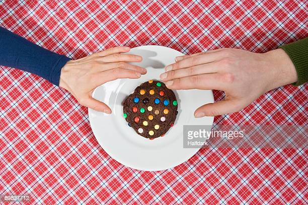 Two hands reaching for a cookie
