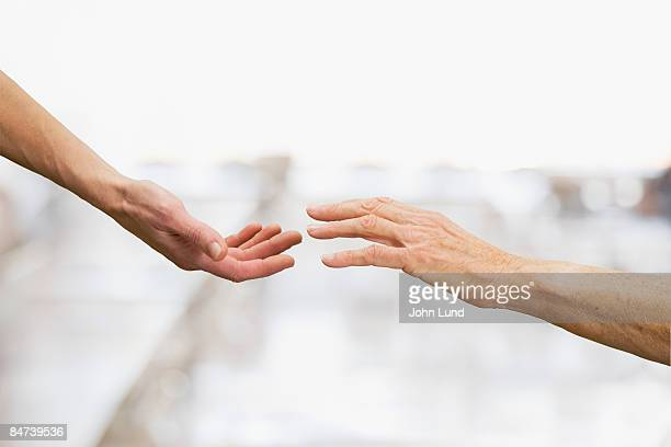 two hands reaching - reaching stock pictures, royalty-free photos & images