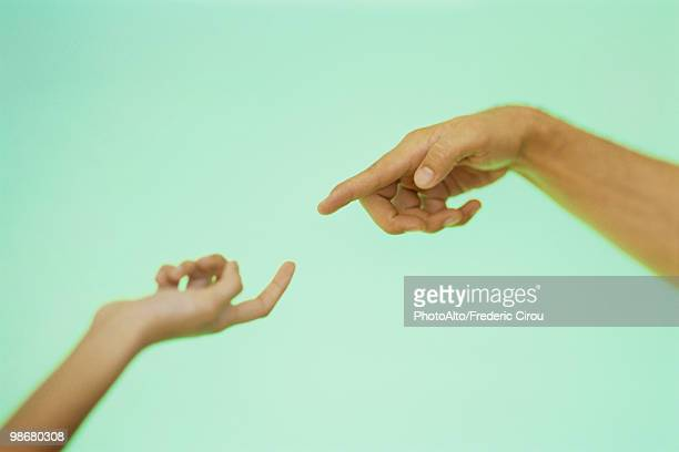 Two hands reaching toward each other with index fingers extended