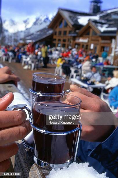 Two hands resting glass mugs on fence, chalet in background, France