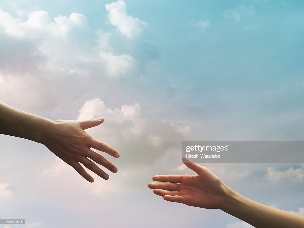 Two hands seem to reach together in the sky : Stock Photo